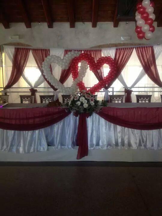 la tavolata di un ricevimento con colori bianchi e rossi e cuori di palloncini sullo sfondo.