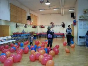 una sala con palloncini rossi e arancio a terra. la location di una delle nostre feste a roma