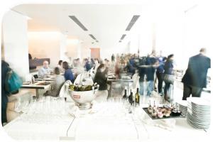 la sala di ricevimento di uno dei nostri eventi aziendali a roma. un tavolo con bottiglie e bicchieri in primo piano e gli ospiti sullo sfondo