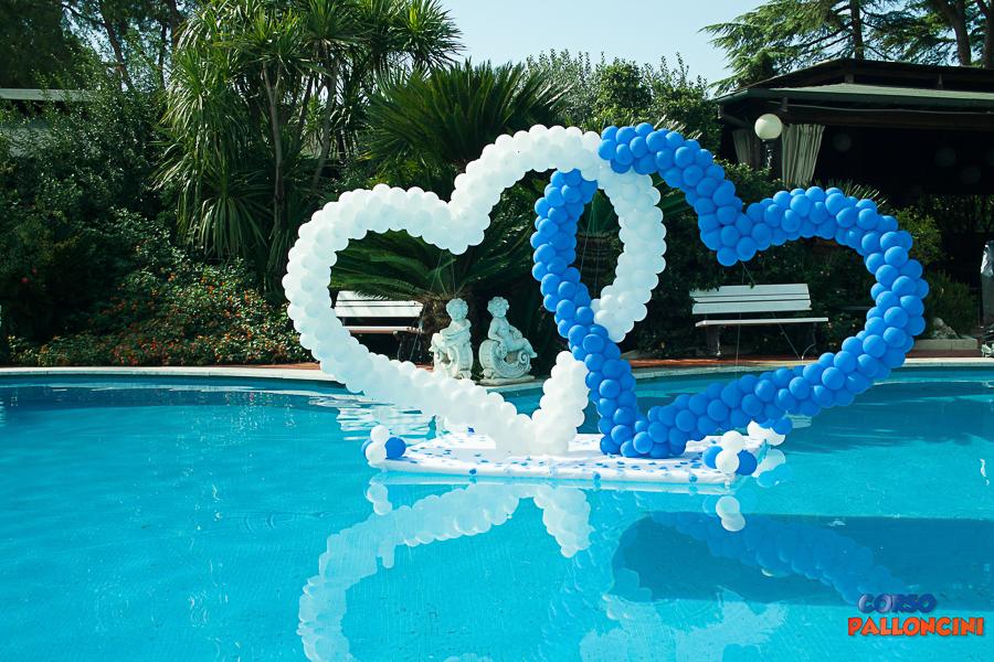 due cuori di palloncini bianco e blu, che galleggiano su una piscina. uno dei nostri allestimenti di palloncini a roma