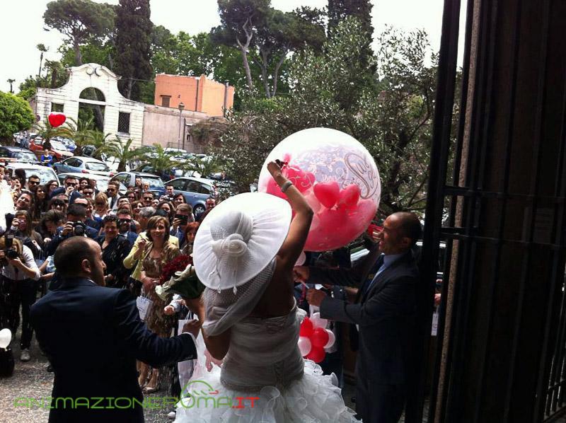 sposa che solleva, all'uscita dalla chiesa, una mongolfiera di palloncini. Uno degli allestimenti di palloncini a Roma di TB Animazione