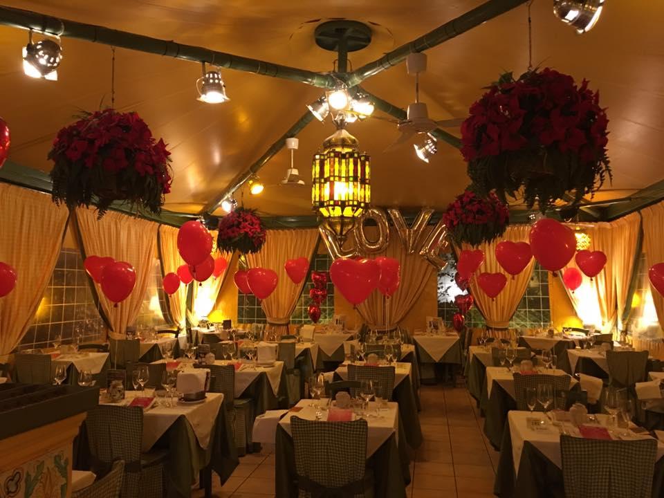 sala di un matrimonio con tavoli bianchi. e palloncini rossi a cuore. location di una coppia che ha scelto uno dei nostri dj matrimonio a roma