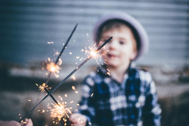 bambino che tiene delle stelline luccicanti durante una delle feste per bambini a Roma di TB Animazione